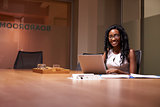 Young black woman working late in office smiling to camera