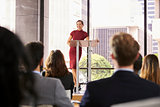 Young woman leaning on lectern presenting business seminar