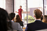 Young woman presenting business seminar gestures to audience