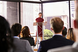 Young woman standing at lectern presenting business seminar