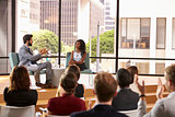 Man and woman talk in front of audience at business seminar