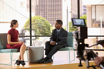 Black man and white woman on set filming a TV interview