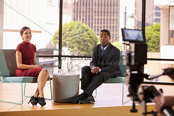 Black man and white woman on TV interview set look to camera
