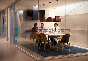 Three people in meeting cubicle at a big corporate business