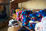 Colourful blankets displayed on shelves in a store, close up