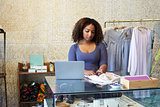 Woman working in clothes shop checking price tag, front view