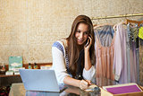 Young woman working in clothing store on phone, front view