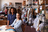 Trainee and manager at clothing design studio look to camera