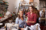 Trainee and manager at clothes design studio look to camera