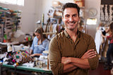 Male business owner in clothing design studio, arms crossed