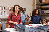 Team packing orders for distribution, woman smiles to camera
