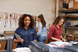 Mixed race woman packing clothing orders smiles to camera