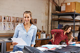 Young woman packing orders for distribution smiles to camera