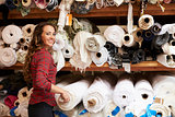 Young white woman selecting fabrics looking to camera