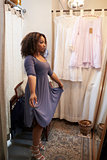 Woman trying on dress in a boutique changing room, vertical