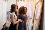 Woman in boutique changing room with friend trying on dress