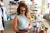 Female business owner using tablet computer in clothes shop