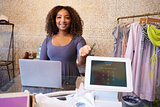 Assistant at clothing store shows computer used for payment