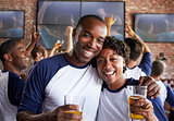 Portrait Of Couple Watching Game In Sports Bar On Screens