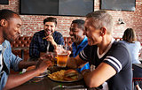 Male Friends Eating Out In Sports Bar With Screens In Behind