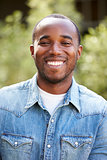 Happy young African American man in denim shirt, vertical