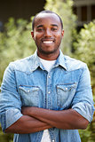 African American man in denim shirt, arms crossed, vertical