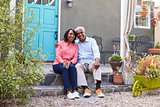 Senior couple sit on steps outside their house, full length