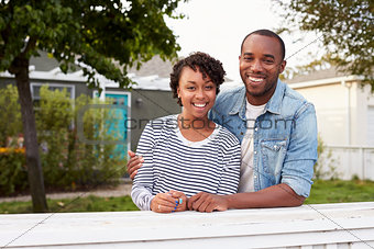 African American couple look to camera outside their house