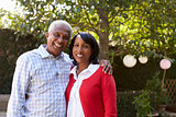 Senior black couple in their garden looking to camera