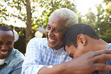 Senior man greeting his two adult sons in garden, close up