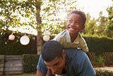 Young black boy playing on his dadÕs back in a garden