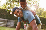 Young black boy playing on dadÕs back in a garden, low angle