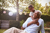 Young black boy embracing grandfather sitting in garden