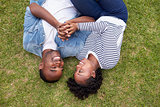 Young black couple lying on grass look at each other, aerial