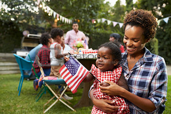 Black mother and baby holding flag at 4th July garden party
