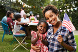 Black mother and baby hold flag at 4th July party, to camera