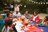 Multi generation black family at table for 4th July barbecue