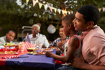 Black father and son at family 4th July barbecue, close up