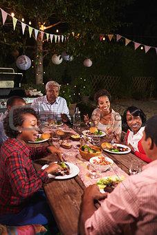 Adult black family enjoy dinner together in garden, vertical