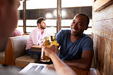 Two male friends in a bar making a toast with beer bottles