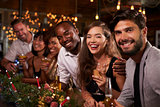 Friends enjoying Christmas celebrations look to camera
