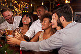Friends at a Christmas party making a toast at the bar