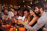 Friends enjoying a Halloween party at a bar making a toast