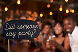 Sign at a party, defocussed celebrations in the background