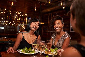 Three female friends enjoying dinner at a restaurant