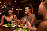 Three female friends enjoying dinner at a restaurant