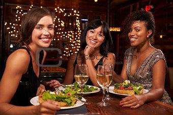 Three female friends at dinner in restaurant look to camera