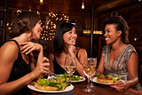 Three female friends eating dinner together at a restaurant