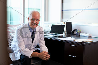 Portrait Of Doctor Wearing White Coat In Office