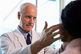 Doctor In White Coat Examining Female Patient In Office